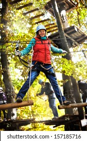 adventure climbing high wire park - people on course in mountain helmet and safety equipment
