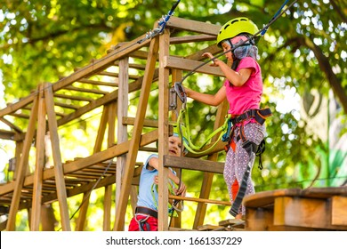 adventure climbing high wire park - children on course rope park in mountain helmet and safety equipment