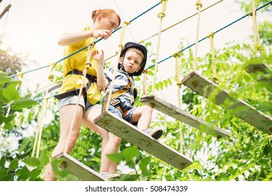 Adventure climbing high wire park - kids on course in mountain helmet and safety equipment