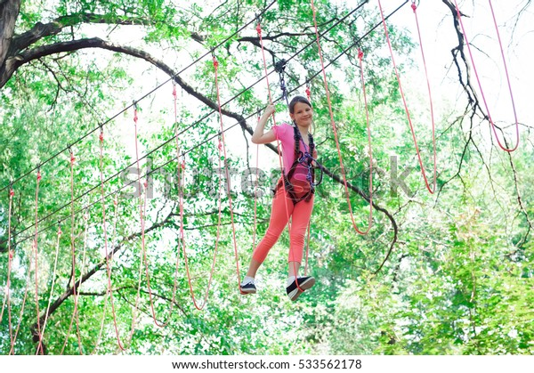 adventure climbing high wire park - hiking in the rope park girl in safety equipment.