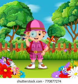 adventure cute boy holding magnifiying glass in a flower garden