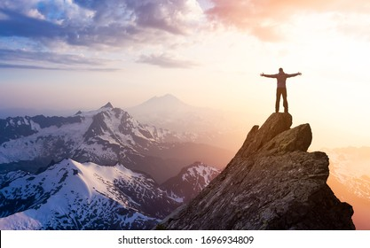 Adventure, Explore and Lifestyle Concept Composite. Adventurous Man Hiker With Hands Up on top of a Steep Rocky Cliff. Sunset or Sunrise. Landscape Taken from Washington, USA.