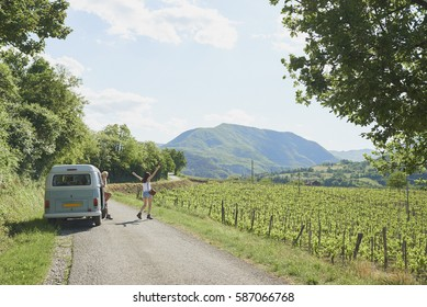 Adventure girl friends on road trip vintage camper van driving through countryside vineyards arms outstretched
