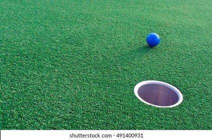 Adventure Golf, ball rolling towards hole.