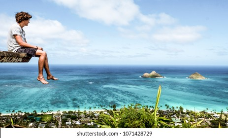 Adventure Guy Sitting on Cliff and Looking the Beautiful Wild Nature with  Ocean Beach View Landscape in Hawaii Island. Young Travel Man Enjoying Relaxing Spending Time this Vacation Holiday Outdoor.