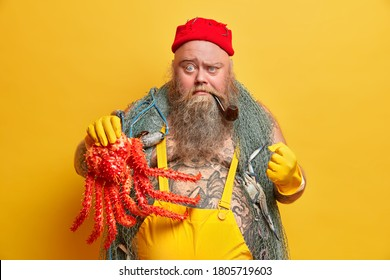 Adventure, hobby, fishing concept. Angry fisherman with serious strict expression clenches fist, shows octopus caught during marine voyage, frowns face, carries fishnet, keeps smoking pipe in mouth
