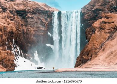 Adventure man by skogafoss waterfall, nature on Iceland. Vatnajokull National Park. Young man visiting nature landscape.