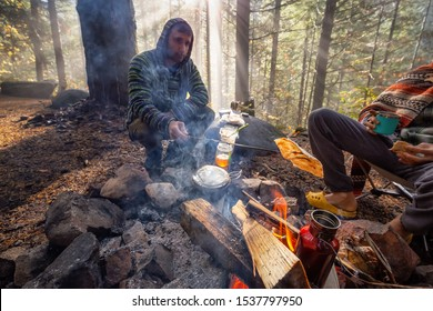 Adventure Man cooking pitas over the camp fire during a foggy morning sunrise in forest. Taken in Sloquet Hot Springs, Located North of Vancouver, British Columbia, Canada.