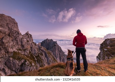 Adventure Man with Dog at High Mountains Peak at Sunrise. Togetherness and Friendship Concept.