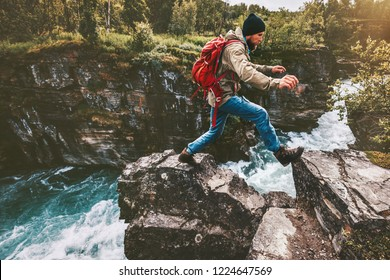 Adventure man jumping on rocks over river canyon traveling active lifestyle concept weekend journey vacations trail running in Sweden wilderness