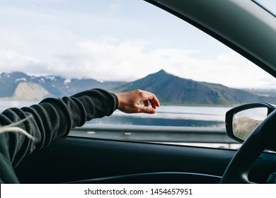 Adventure mood, wanderlust nomad travel blogger lifestyle concept. Woman holds out hand out of window while driving car on roadtrip through scandinavia, forever young inspiration for road