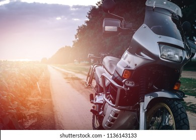 Adventure Motorcycle standing on a dirt road at the suset, off road travel concept, enduro rider equipment, extreme lifestyle, copy space