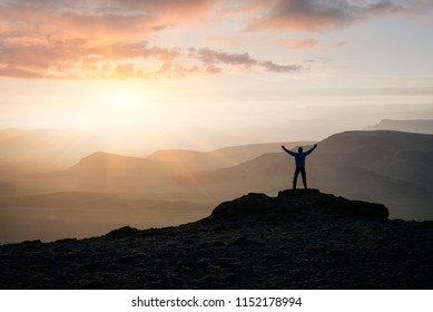 Adventure in the mountains of Iceland. Tourist is standing on a rock against the background of the setting sun. Location near Dyrholaey Cape in southern Iceland