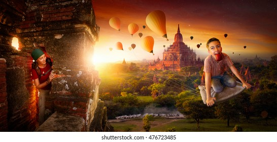 Adventure naughty boy stealing balloons on a magic carpet ride in Bagan (Myanmar) at sunrise. Funny concept of traveling and active lifestyles of young people.