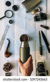 Adventure planning flat lay. Travel vintage gear on map. Traveler, explorer hands in frame pouring coffee or tea from thermos into mug. Vertical exploring, hiking poster, postcard, template.