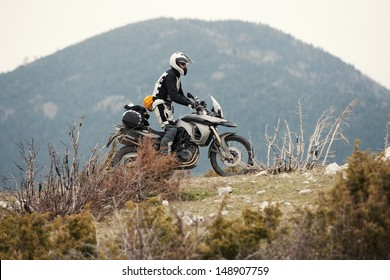 Adventure rider traveling, outdoor shot. Strong grain.