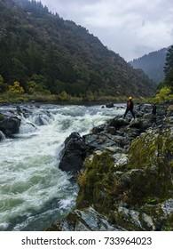 Adventure seekers standing on rocky riverbank at Rainy Falls, Oregon.