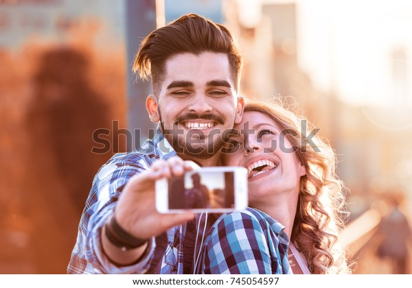 Adventure Selfie.Caucasian young loving couple taking selfie while walking in the city.