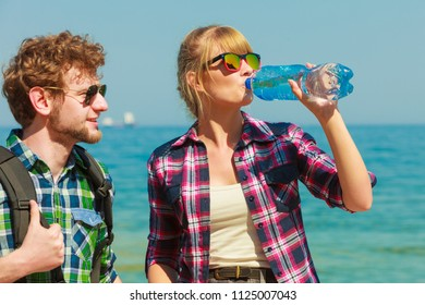 Adventure, summer, tourism active lifestyle. Young couple backpacker tramping by seaside, girl drinking water from plastic bottle