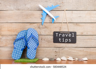 "Adventure time - blackboard with text ""Travel tips"", plane, seashells on brown wooden background"
