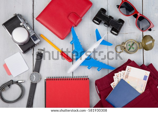 Adventure time - plane, passport, money, camera, compass, headphones, sunglasses, binoculars, jeans, notepad, wallet on white wooden table