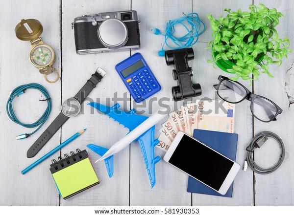 Adventure time - plane, passport, money, camera, compass, headphones, binoculars, watch, smartphone, calculator, glasses on white wooden table