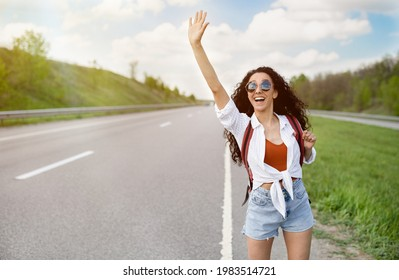 Adventure and tourism concept. Beautiful millennial woman in casual wear waving down car, hitchhiking on roadside, copy space. Pretty young lady traveling by autostop, having summer trip
