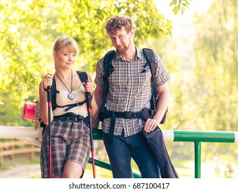 Adventure, tourism, enjoying summer time. Hiking young couple with backpacks tramping on forest road