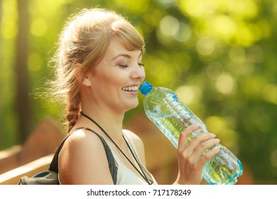 Adventure, tourism, enjoying summer time - young tourist hiker woman with plastic water bottle in forest trail