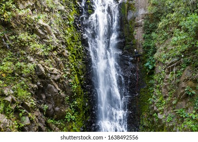 Adventure tourism in tropical Costa Rica with a young man rappelling down a beautiful waterfall  deep in the southern mountains of the country
