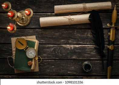Adventure or travel concept background. Diary book of treasure hunter, golden compass, candle and ancient manuscripts on aged wooden table background with copy space.