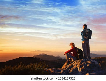 adventure travel, couple of hikers relaxing on top of mountain, active tourism with backpack