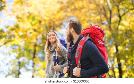 adventure, travel, tourism, hike and people concept - smiling couple walking with backpacks over natural background