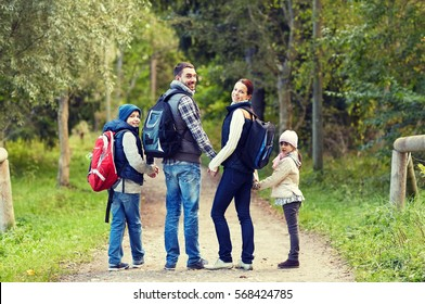 adventure, travel, tourism, hike and people concept - happy family walking with backpacks in woods and looking back