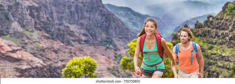 Adventure travel tourists hiking outdoors in mountain nature landscape banner. Panoramic crop of young people hikers happy walking together, multiracial couple.