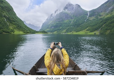 Adventure woman in row boat taking photo on smart phone of beautiful fjord lake for social media