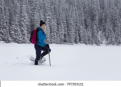 Adventure woman is snowshoeing in the beautiful Canadian Snow Covered Landscape in the winter time. Taken in Joffre Lake, North of Vancouver, British Columbia, Canada.
