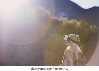 Adventure woman wearing vr headset augmented virtual reality in beautiful outdoor landscape concept sunset flare