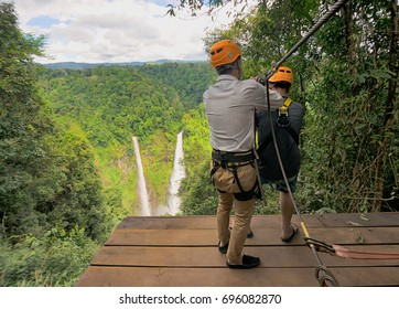 adventure zipline high wire park - people on course in mountain helmet and safety equipment,ready to descend on zipline in forest, extreme sport