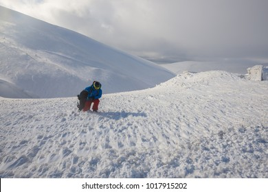 Adventurer, with backpack and snowboard in his hands, rises up the mountain peak during a blizzard. Awesome freeride in a winter mountains.