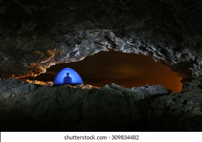 Adventurer camping in a blue tent during a beautiful night in a cave out in nature.