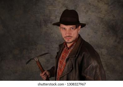 Adventurer explorer with fedora hat is holding pickax