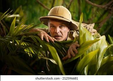 Adventurer hiding and peeking through plants in the rainforest jungle with exploration equipment.