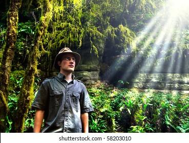 An adventurer looking at sun light in a jungle
