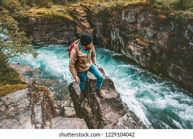 Adventurer man hiking alone active lifestyle extreme vacations outdoor on cliff above river canyon in Sweden