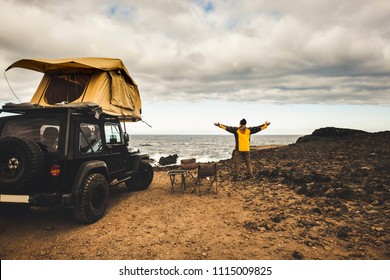 adventurer man in journey travel with off road car and roof tent to enjoy freedom and explorer concept. discover the world living near the power of the nature. ocean coast home view. driving around