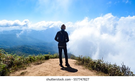 Adventurer man standing on the edge of a cliff with clouds ahead. Mountains and clouds in the background that is far away.