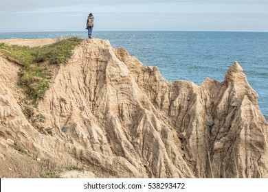 An adventurer marvels at the Atlantic Ocean from the edge of a bluff.