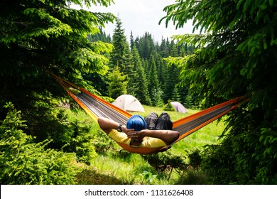 Adventurer relaxes in hammock on the green mountain meadow among fir trees and admires view. Epic travel in the mountains. Back view.
