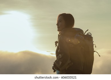 The adventurer stands at the top of the mountain with foggy morning sky with the shadow of a distant mountain,freedom lifestyle concept traveller with backpacks relaxing.